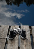 Black teenager's shoes standing on the bridge edge, choice concept Stock Image