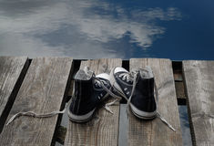 Black teenager's shoes standing on the bridge edge, choice concept Stock Photography