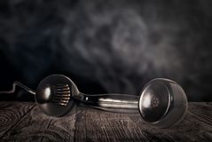 Black telephone receiver on a wooden table. With a dark background royalty free stock images