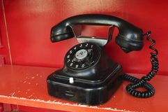 Black telephone set in red phone box Stock Images