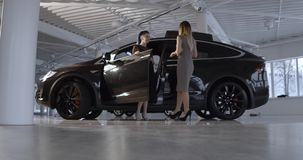 Black Tesla electric car model X in the promotion showroom. Side view full size image of Tesla car Model X in showroom. Two women standing by. Electric cars stock footage