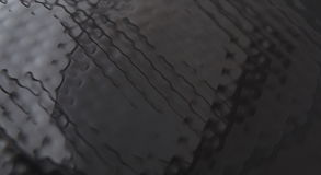 Black textured background. Abstract black textured background closeup. Wavy surface reflecting light Stock Photos