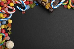 Black textured background with colorful dragee. Black textured background with mix of colorful dragee with raisins or peanuts inside, marmalade or jelly candies Stock Photo