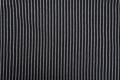 Black textured knitted fabric with white stripes. Vertical pattern.  stock photo