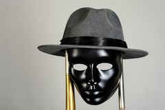 Black theater mask and hat hanging on a brass pipe. On gray background with copy space. Social masking and mystery concept Stock Photography