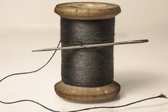 Black thread with a needle on an ancient antique old wooden coil Royalty Free Stock Photos