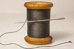 Black thread with a needle on an ancient antique old wooden coil closeup white background Royalty Free Stock Images
