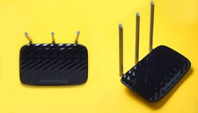 Black Three-antenna wi-fi router. Isolated on yellow background. Set of two different foreshortenings stock photos
