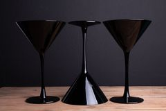 Black on black: three elegant black glass martini glasses on black tablecloth and black (one glass upside down) stock photos