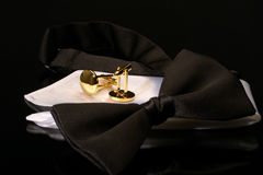 Black tie. Deluxe black bow tie, white silk pocket handkerchief and gold cufflinks on a glass surface stock photos