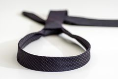 Black tie knotted in a loop shape on a white background. The con royalty free stock photography