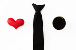 Black tie, red heart and hot coffee on white background, love wo. Rking, love my job, valentines day concept royalty free stock photography