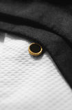 Black Tie White Shirt. Black silk bow tie lying across a white cotton formal dress shirt, with gold shirt stud royalty free stock photos
