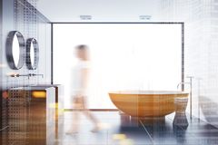 Black tile bathroom, wooden tub and sink toned. Woman in a panoramic bathroom interior with black tile walls, a wooden bathtub and a double sink with two round stock image