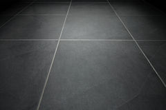 Black tile flooring. Close up as background Stock Images