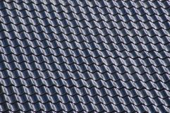 Black tiles aligned on a roof. In a regular pattern stock photography