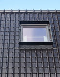 Black tiles of a new roof with an inserted window. Tiles are glossy royalty free stock photos