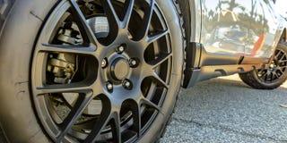 Black tire rim and disc brake of a shiny white car royalty free stock photo