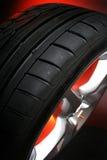 Black tire. wheel. Sport black car tire on red/black Royalty Free Stock Photo