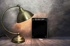 Black to do list with lamp, dark stock photography