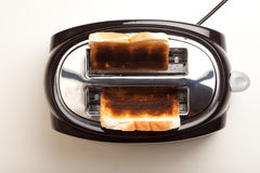 Black toaster, two burnt black slices of bread Royalty Free Stock Image