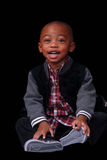 Black Toddler smiling. Black or African American child in a red plaid shirt on a black background posing with a big smile stock images