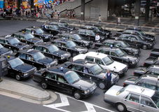 Black Tokyo taxis in rows. Rows of Tokyo taxis in front of a train station Stock Image