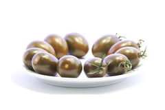 Black tomatoes ingredient on white plate Stock Photography