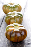 Black tomatoes on wooden table Stock Photos