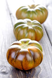 Black tomatoes on wooden table Royalty Free Stock Photography
