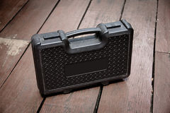 Black toolbox. Plastic black toolbox on wooden floor Royalty Free Stock Photos