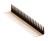 Black toothed hair comb. Photographed balancing upright with the teeth in the air casting a shadow on a white background Royalty Free Stock Image
