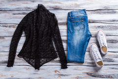 Black top and blue jeans. Stock Photography