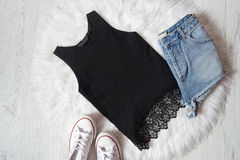 Black top with lace, denim shorts and sneakers on white fur, wooden background. Fashionable concept Royalty Free Stock Photo