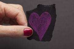 Black torn piece of paper with purple heart shape in woman's han Stock Image