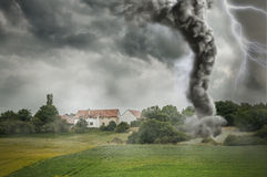 Black tornado funnel and lightning over field Royalty Free Stock Image