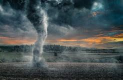 Black tornado funnel over field during thunderstorm Royalty Free Stock Images