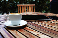 Black touch screen computer on cafe table with coffee cup Royalty Free Stock Image