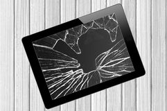 Black Touch Screen Tablet with broken screen over wooden Royalty Free Stock Photography