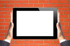 Black Touch Screen Tablet in woman hands over brick wall Royalty Free Stock Images