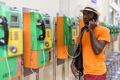 Black tourist man talking on payphone while thinking. Young black African tourist man talking on payphone while thinking and looking up inside the railway royalty free stock photography
