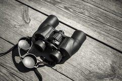 Black touristic binoculars lays on wood Royalty Free Stock Images