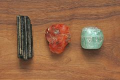 Black tourmaline, Sherl, Carnelian, Beryl, Emerald. Collection o. F natural stones of minerals on a background of natural wood American black walnut. Beautiful stock photo