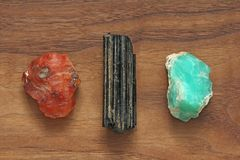 Black tourmaline, Sherl, Carnelian, Chrysoprase. Collection of n. Atural stones of minerals on a background of natural wood American black walnut. Beautiful stock photos