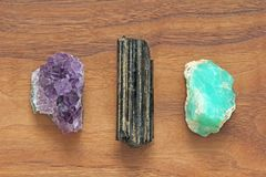Black tourmaline, Shirl, Amethyst, Chrysoprase. Collection of na. Tural stones of minerals on a background of natural wood American black walnut. Beautiful royalty free stock image
