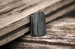 Black tourmaline. Shorl - rough black tourmaline quartz piece on a  wooden background Royalty Free Stock Photos