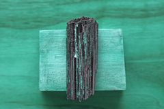 Black tourmaline stone on a background of natural wood American. Black walnut. Mineral collection stones. Stone is a sherl tourmaline. Black Crystal stock photos