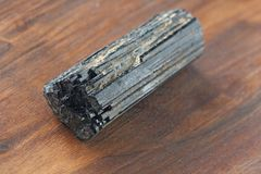 Black tourmaline stone on a background of natural wood American. Black walnut. Mineral collection stones. Stone is a sherl tourmaline. Black Crystal royalty free stock photos