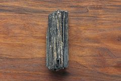 Black tourmaline stone on a background of natural wood American. Black walnut. Mineral collection stones. Stone is a sherl tourmaline. Black Crystal royalty free stock images
