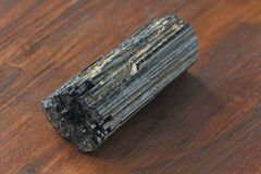 Black tourmaline stone on a background of natural wood American. Black walnut. Mineral collection stones. Stone is a sherl tourmaline. Black Crystal royalty free stock image